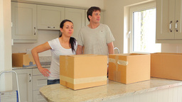 Couple proudly put moving boxes in the kitchen Stock Video Footage
