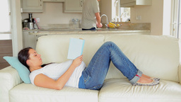 Pregnant woman relaxing on sofa with book Footage