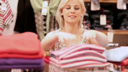 Woman folding clothes and smiling Footage