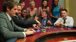 Men placing bets at roulette table watched by wome Footage
