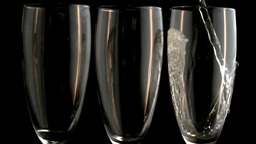 Three champagne flutes with one being filled Footage