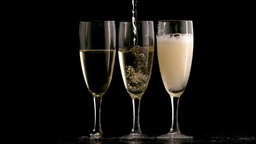 Three champagne flutes topped up Footage