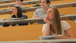 Student sitting at the lecture hall holding a tablet pc Stock Video Footage