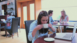 Brunette drinking coffee and using laptop Footage