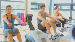 Video of three people working out on row machines Footage