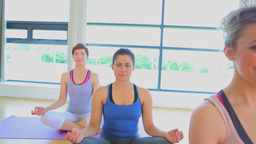 Smiling women sitting on yoga mats at yoga class Stock Video Footage