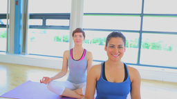 Smiling women sitting on yoga mats at yoga class Footage