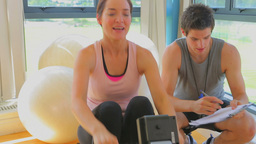 Happy woman at the rowing machine supporting by a  Footage