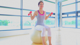 Woman sitting on a exercise ball with dumbells Footage