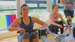 Women at the rowing machine supporting by a coach Stock Video Footage