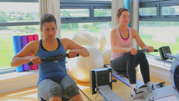 Women at the rowing machine supporting by a coach Footage