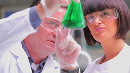 Chemists viewing green liquid Footage