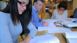 Woman studying in library with a group Stock Video Footage