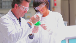 Chemist holding up a green liquid Stock Video Footage