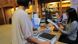 Librarian scanning book and handing to woman Footage