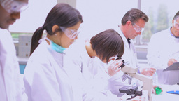 Man viewing liquid while other chemists doing rese Stock Video Footage