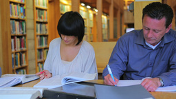 Man and woman writing in library Stock Video Footage