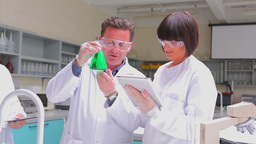 Chemist mixing green liquid in beaker with two che Stock Video Footage
