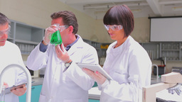 Chemist mixing green liquid in beaker with two chemists... Stock Video Footage