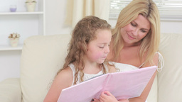 Video of mother and daughter reading a book Stock Video Footage