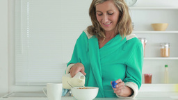 Woman pouring milk into cereal Stock Video Footage