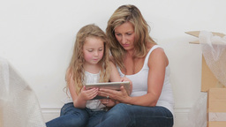 Video of mother and daughter sitting on the floor with tablet computer Footage