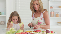 Mother and daughter preparing vegetables Footage