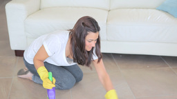Video of woman scrubbing the living room floor Footage