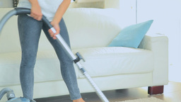Woman standing holding a vacuum cleaner Stock Video Footage