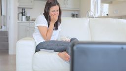 Laughing woman watching television Footage
