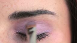 Woman putting on purple eyeshadow Live Action