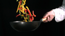 Peppers being tossed in a wok ビデオ