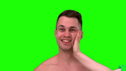 Smiling man taking a slap on green background Footage