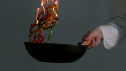 Peppers being tossed in a flaming wok Stock Video Footage