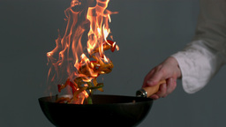 Peppers being tossed in a flaming wok ビデオ