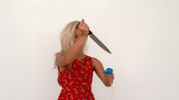 Woman popping a balloon with knife Footage