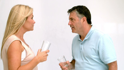 Couple throwing glasses of water at each other Stock Video Footage