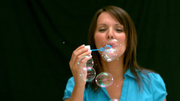 Woman blowing bubbles on black background Stock Video Footage
