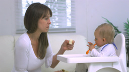Mother feeding her child banana Stock Video Footage