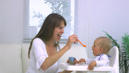 Mother feeding baby in highchair Footage