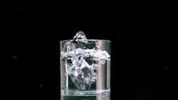 Ice cube falling in glass Stock Video Footage