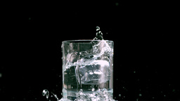 Ice cube overfilling a glass Stock Video Footage