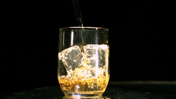 Whiskey being poured into a glass with three ice c Footage