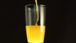 Orange juice filling a big glass Stock Video Footage