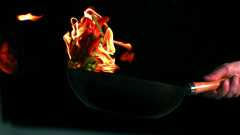 Chef tossing flaming pan of peppers ビデオ