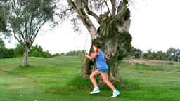Girl running around a big tree Footage