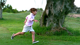 Young boy running around a big tree with sister Footage
