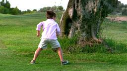 Two children running around a big tree Footage