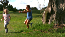 Little girl running after a little boy around a tr Footage