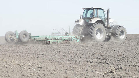 gray tractor go on black earth field Footage